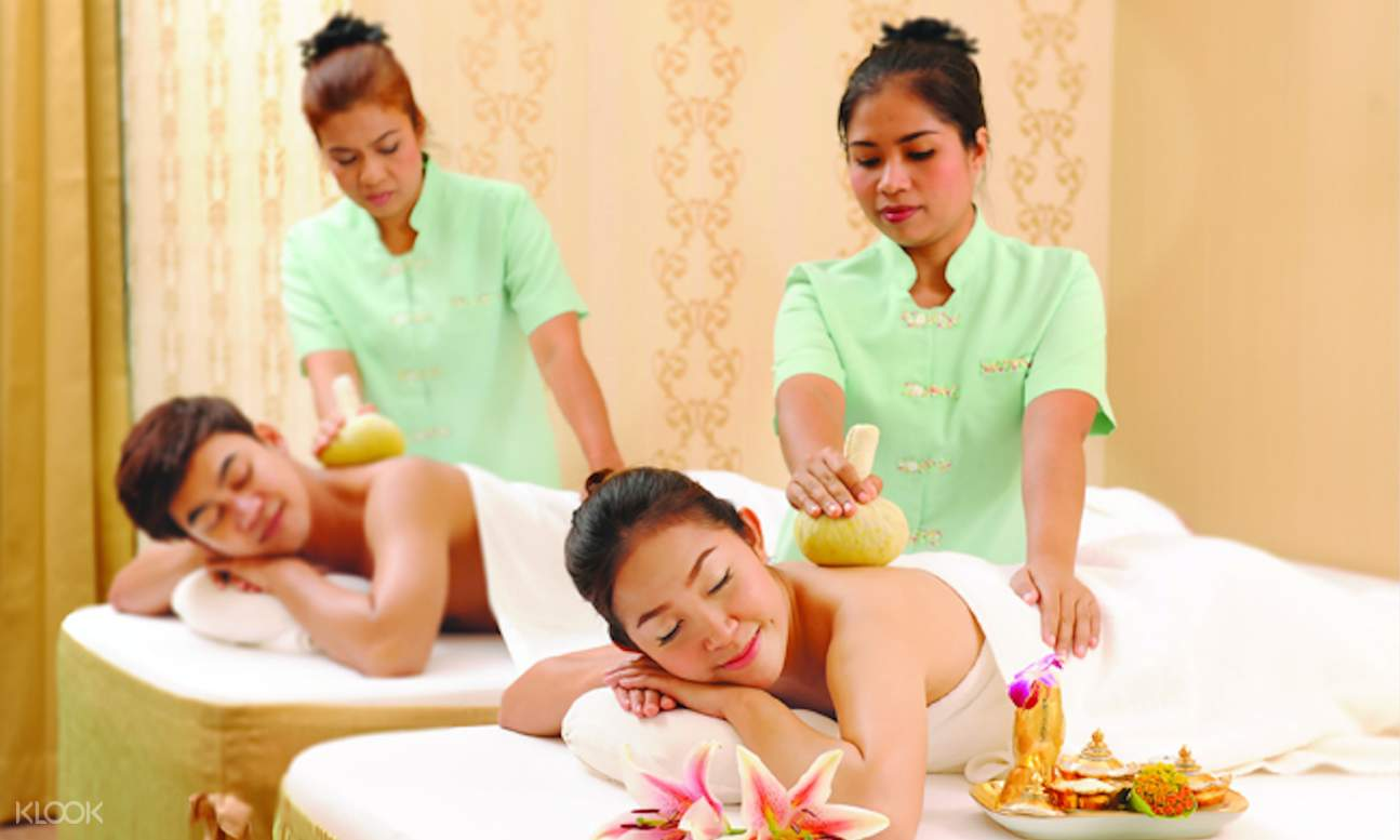 man and woman receiving herbal ball massage treatment